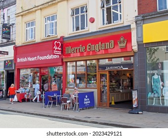 brighouse, west yorkshire, united kingdom - 21 july 2021: commercial street in brighouse with people outside the british heart foundation and merrie england coffee shops