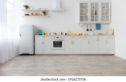 Bright accessories and modern style of kitchen interior. White furniture with utensils, colored cups and kettle, shelves with dishes and plants in a pots, refrigerator in dining room, empty space