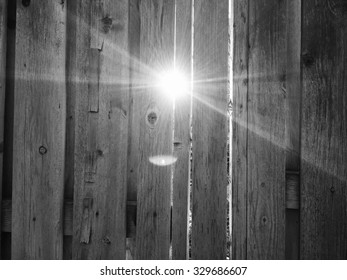 Bright afternoon light shines through the slats and wooden fence on the first day of spring in Salt Lake City, Utah