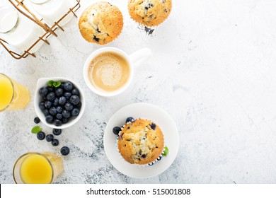 Bright and airy breakfast with blueberry muffin, big cup of coffee and milk in bottles overhead view with copyspace