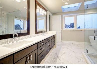 Bright and airy master bathroom features White Modern Double Vanity With Rich Brown Cabinets accented with mosaic backsplash and paired with marble floor. Northwest, USA