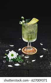 Bright alcohol cocktail with ginger garnish with ice, and flower on black background