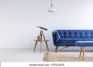 Appartement lumineux avec canapé bleu, banc, tapis, lampe et table