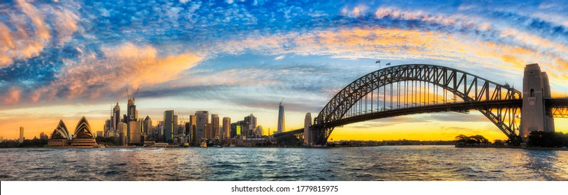 Bright arch of sun light at sunset over Sydney city CBD landmarks and Harbour bridge in wide panorama.