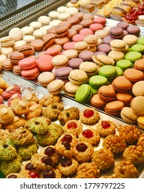 Bright assortment of the sweet french delights on display. So called petit fours: macaron, eclair and range of cookies. Different pastel colors. On display.