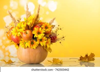Bright autumn bouquet in a pumpkin on yellow background