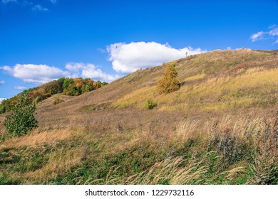 Bright autumn landscape with an orthodox cross on a mountain on a sunny day, Russia.