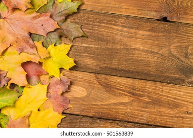 Bright autumn leaves on a wooden background. Autumn background.