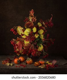 Bright autumn still life with yellow flowers and red viburnum berry bouquet on  dark background