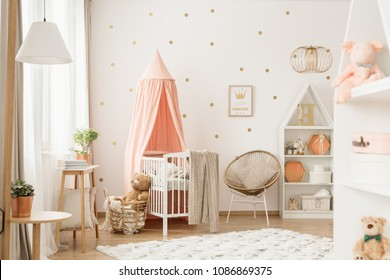 Bright baby girl room interior with decor, toys and white wooden crib with pastel pink canopy