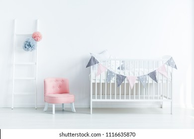 Bright baby room interior with a crib decorated with triangles on a rope, pink seat and ladder with pompoms
