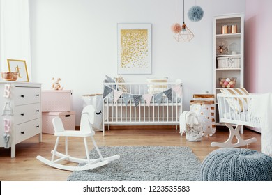 Bright baby room with white furniture, grey carpet on the floor and golden painting on the empty wall, real photo