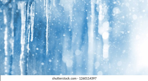 Bright background with icicles. Winter background with icicles and falling shiny snow