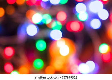 A bright background with shiny lights of different colors: white, red, purple, yellow, orange. Dark backdrop
