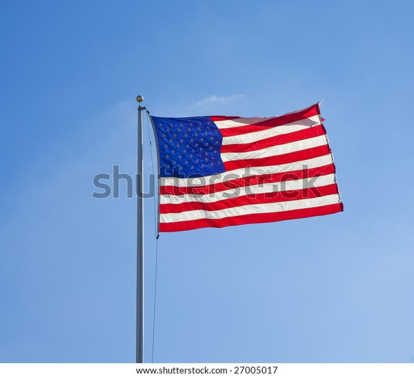 A bright, backlit american flag on a blue sky