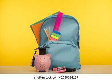 Bright backpack with school tools and piggy bank in hat. Savings for education concept