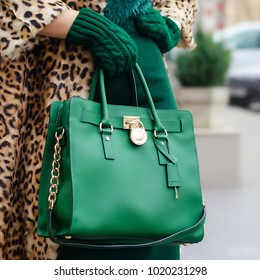 A bright bag in women's hands. Leather bag. Close-up. Green mittens, green bag and leopard coat. Women's accessories. bags