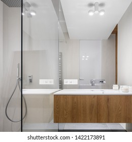 Bright bathroom with big mirror and wooden basin cabinet