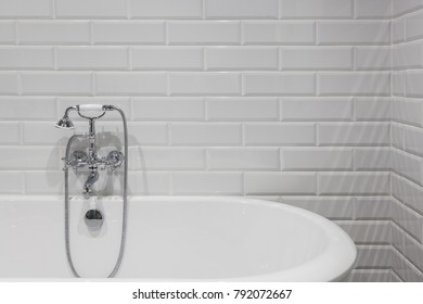 Bright bathroom with new tiles. Chrome shower, faucet, white bathroom
