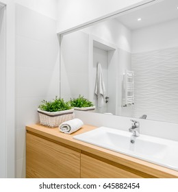 Bright bathroom with structural white tiles, wooden cabinet and big mirror