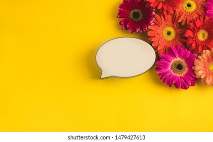 Bright beautiful gerbera flowers and bubble speech on sunny yellow background. Mother's Day, Valentine holiday. Place for text, lettering or product. View from above, Copy space. Flatlay