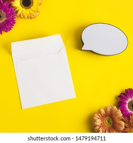 Bright beautiful gerbera flowers and paper card, bubble speech on sunny yellow background. Mother's Day, Valentine holiday. Place for text, lettering or product. View from above, Copy space. Flatlay