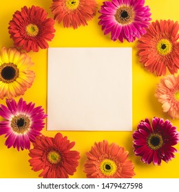 Bright beautiful gerbera flowers and paper card on a sunny yellow background. Mother's Day, Valentine holiday. Place for text, lettering or product. View from above, Copy space. Flatlay