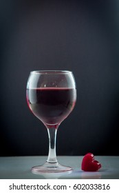bright beautiful red wine pouring jet into a transparent glass cup isolated on a wite background