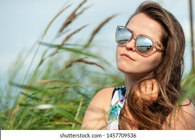 Bright beautiful and young brunet girl in sunglasses enjoying the nature under blue sky - close up on pretty face with smile and skies reflection in sunglasses
