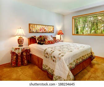 Bright bedroom with brown carpet floor. Furnished with bed, covered round table and cabinet