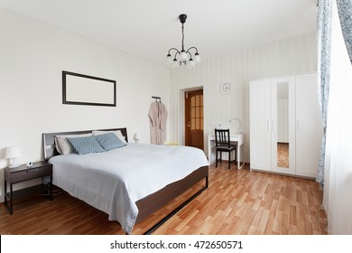 Bright bedroom with double bed and small workplace. Interior design