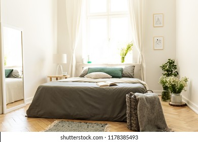 Bright bedroom interior with green decor of a cushion and bunches of wild flowers. Big bed against a sunny window in a villa. Real photo.