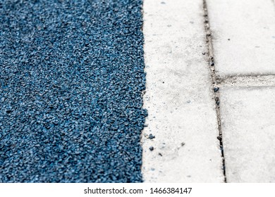 bright blue asphalt bordered on a gray brick road; photo shows the contrast and the difference between them