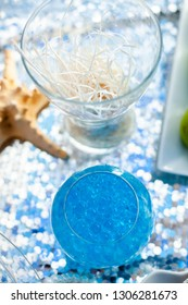 Bright blue balls in the glass vase. Seatime theme on the party's candybar.