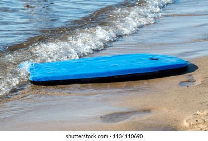 A bright blue beach board washes up on the shore at a beach on Lake Michigan