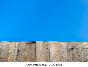 A bright blue cloudless sky over a light brown wooden garden fence.