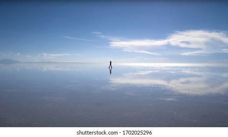 Bright Blue Cloudy Sky Over Salar de Uyuni, Bolivia, South America. Vast Desert With Reflection On Water And Dry Mountains. Colorful Landscape In Wilderness.