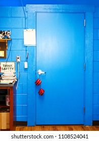 Bright blue door in computer classroom with Think Safety sign and stack of manuals - fuzzy dice hanging from door handle