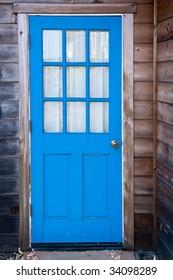 Bright blue door of a Mendocino cabin