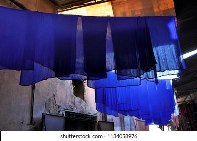 Bright blue fabrics hang on ropes. Ultramarine berber shawls dry after staining. Narrow street of the medina of Marrakech. Morocco.