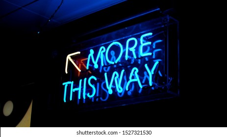 A bright blue fluorescent 'More This Way' neon sign with a yellow arrow pointing upwards. The neon sign illuminates its surroundings making this a key feature to the growing establishment