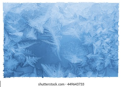 Bright blue frost pattern on a window glass in a white frame (as an abstract winter background), retro style