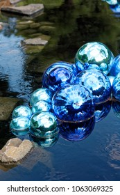 Bright Blue Glass Balls Chihuly Sculpture Sitting in the Water, Reflection Visible, in the Denver Botanic Gardens in Denver, Colorado (Dale Chihuly Traveling Exhibit)