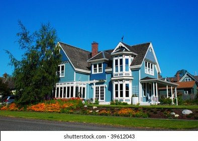 Bright blue house in sunlght with colorful poppies and some graceful trees