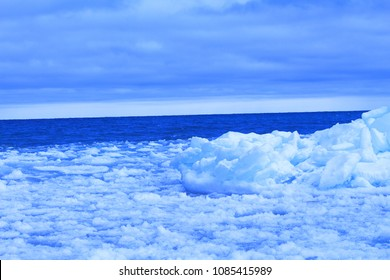 Bright blue ice wall on the shores of Nottawasaga Bay in Meaford, Ontario. These images show the wall in both close-ups and from further away. The ice has a blue tint and the sky and water are vivid.