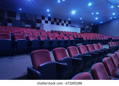 Bright blue light with black armchairs in movie theater