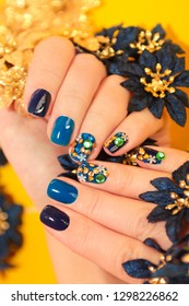 Bright blue manicure with the design of rhinestones of different shapes and colors on the nails close up. Nail art.