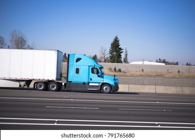 Bright blue modern road train of the semi truck and the dry van trailer streamlined aerodynamic skirt on the highway with lots of traffic lanes separated by markings and concrete fence. Side view.