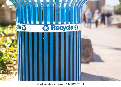 Bright blue recycling bin on street during pleasant warm weather.