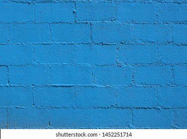 Bright blue rough cinder block wall. Background and texture, copy space